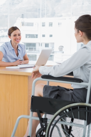 Businesswoman interviewing disabled job candidate in her office and smiling photo