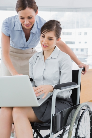 tied down: Businesswoman looking at co workers laptop who is sitting in wheelchair in the office