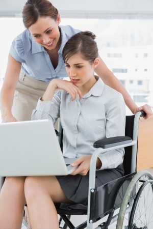 Disabled businesswoman showing colleague her laptop in the office photo