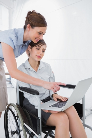 Disabled businesswoman looking at laptop with colleague in the office photo