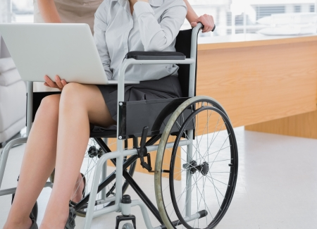 Disabled businesswoman showing laptop to colleague in an office photo