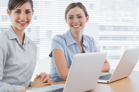 Happy businesswomen with laptops smiling at camera in office photo