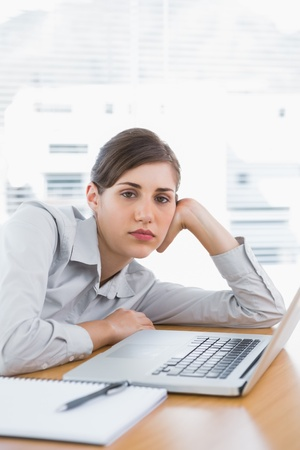 slumped: Fed up businesswoman looking at camera at her desk Stock Photo