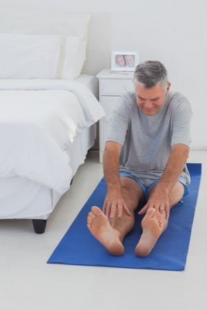 Mature man working out on mat in his bedroom Stock Photo