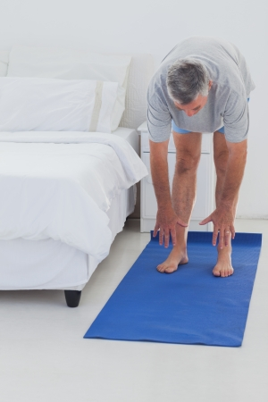 Man stretching on a mat in his bedroom photo