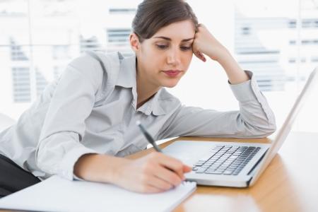 agotado: Empresaria aburrida escribiendo en su escritorio en la oficina Foto de archivo