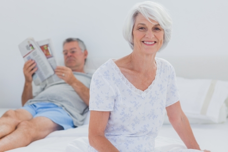 Mature woman sitting on bed while husband is reading a newspaper on the background photo