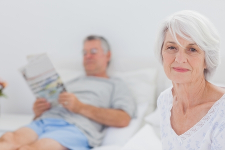 Smiling mature woman sitting in bed with husband reading a newspaper on the background photo