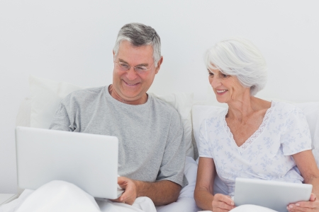 Mature man showing something on his laptop to his wife on bed photo