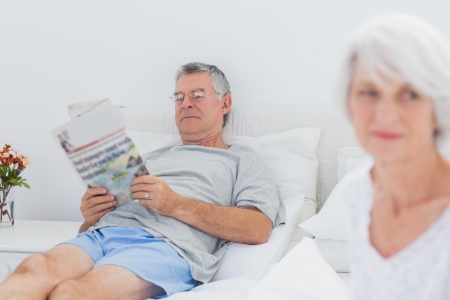 Mature man reading a newspaper in bed while his wife is sitting on bed photo