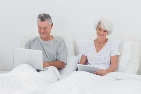 Mature man using a laptop next to wife using a tablet in bed photo