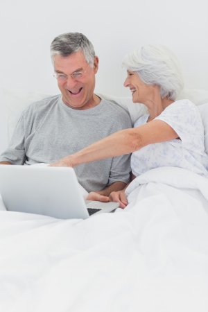 Mature woman pointing at husbands laptop in bed photo