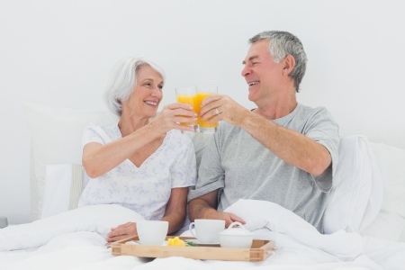 Mature couple having breakfast in bed photo