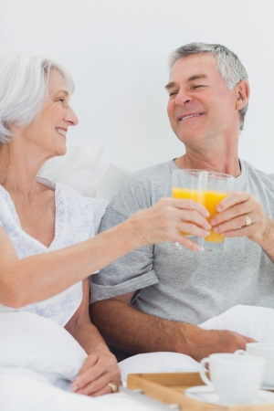 Couple clinking their orange juice glasses while having breakfast in bed photo