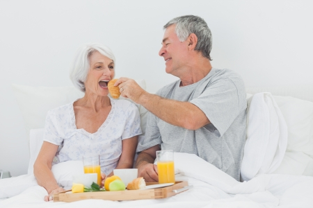 Man giving wife a croissant to wife while they are having breakfast in bed photo