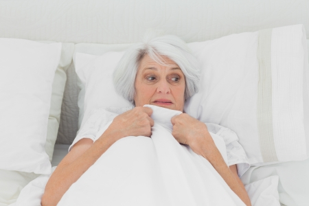 clutching: Fearful woman clutching her quilt in bed