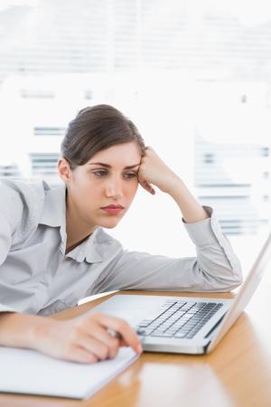 Fed up Unternehmerin auf ihrem Schreibtisch schaut auf Laptop