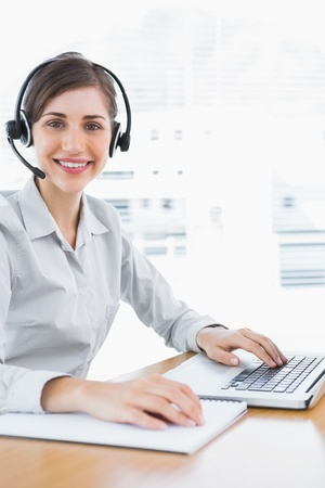 Pretty call centre agent working at desk and smiling at camera photo