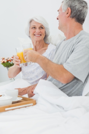 Mature couple clinking their orange juice glasses while they are having breakfast in bed photo