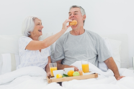 Woman giving husband a croissant while they are having breakfast in bed photo