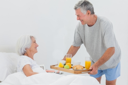 Mature man bringing wife breakfast in bed with orange juice and a croissant photo
