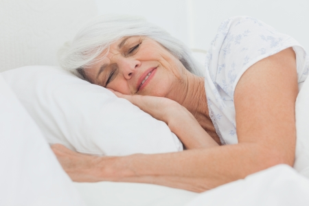 Peaceful woman sleeping in bed at home photo