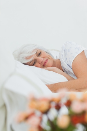 Peaceful mature woman sleeping in bed photo