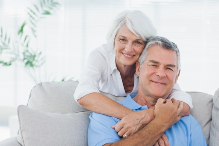 retired couple: Mature woman embracing husband sitting on the couch