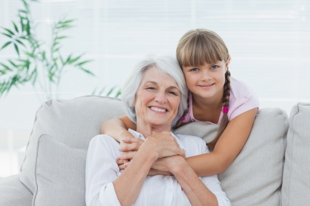 Little girl hugging her grandmother sitting on the couch Stock Photo - 20638479