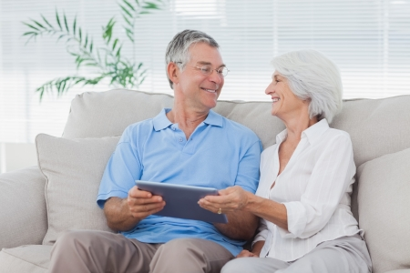 Mature couple using a tablet pc sitting on the couch photo