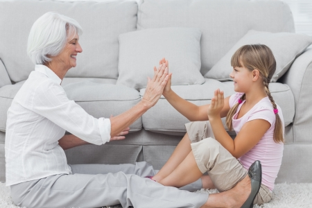 Young girl and grandmother playing together sat on a carpet in the living room Stock Photo - 20638980