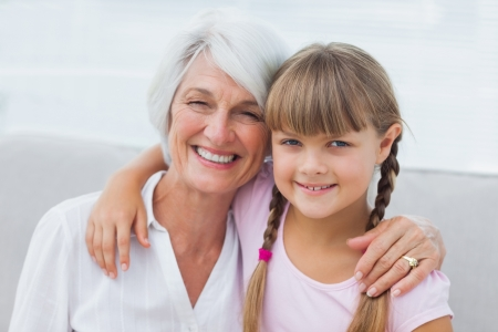 Cute girl and granny sitting on the couch in the living room Stock Photo - 20637016