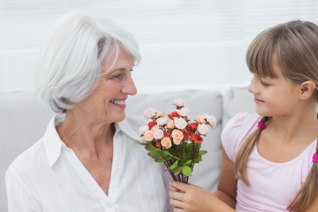 Cute girl giving a bunch of flowers to her grandmother sitting on the couch photo