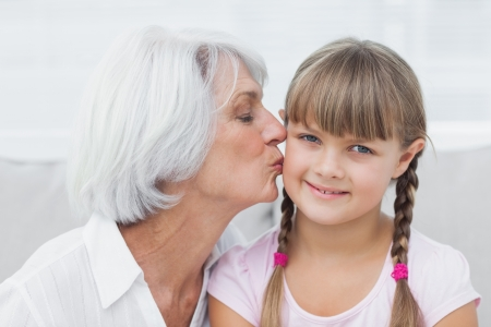 Grandmother kissing her cute granddaughter sitting on the couch Stock Photo - 20629571