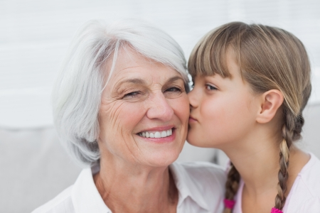 head home: Portrait of a cute little girl kissing her grandmother