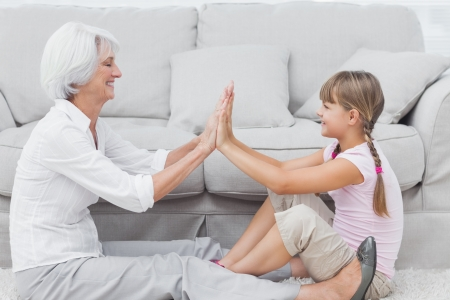 Little girl and grandmother playing together while they are sat on a carpet in the living room photo