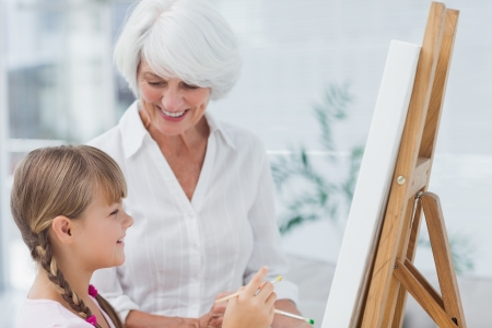 Grandmother and cute granddaughter painting together at home Stock Photo - 20637807