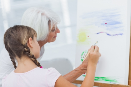 Grandmother teaching granddaughter how to paint at home photo