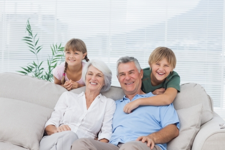 Grandchildren and grandparents sitting on couch in living room Stock Photo - 20639478