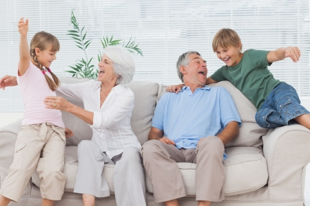 Grandchildren jumping on couch with their grandparents in the living room photo