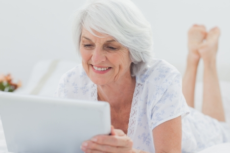 Mature woman lying on bed and using a tablet photo