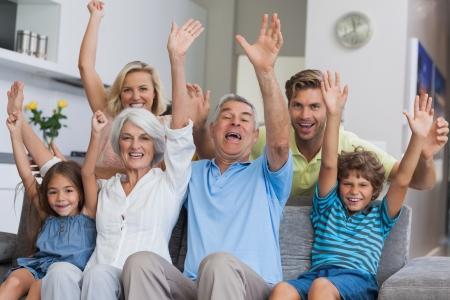 Famille sur plusieurs générations d'élever leurs armes ensemble dans le salon