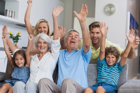 cheer: Multi-generation family raising their arms together in the living room