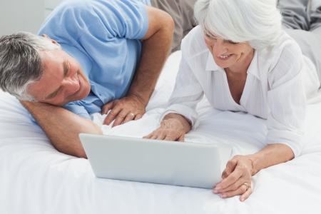 Cheerful mature couple using a laptop in bed photo