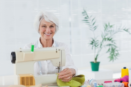 Cheerful retired woman using the sewing machine at home photo