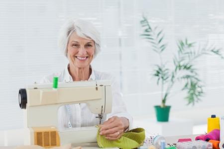 Mujer jubilada alegre que usa la m�quina de coser en su casa photo