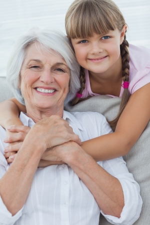 Young girl hugging her grandmother in the couch Stock Photo - 20639458