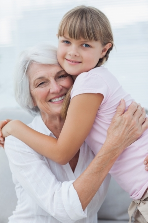 Cute girl hugging her grandmother in the couch Stock Photo - 20637491