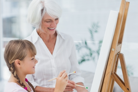 Cheerful grandmother and granddaughter painting together at home Stock Photo - 20637971