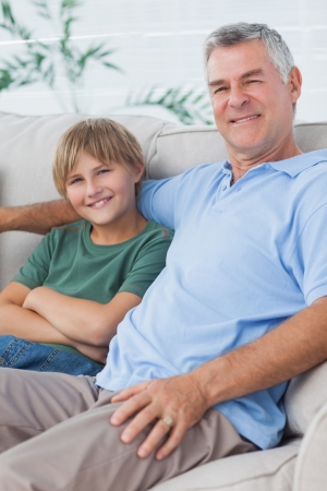Portrait of grandson and grandfather sitting on the couch in the living room Stock Photo - 20639133
